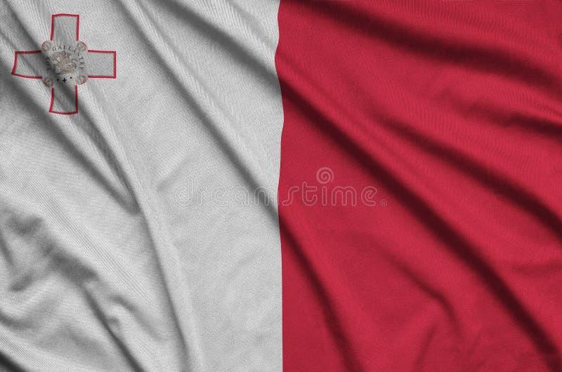 A bandeira de Malta é descrita em uma tela de pano dos esportes com muitas dobras Bandeira da equipe de esporte imagem de stock royalty free