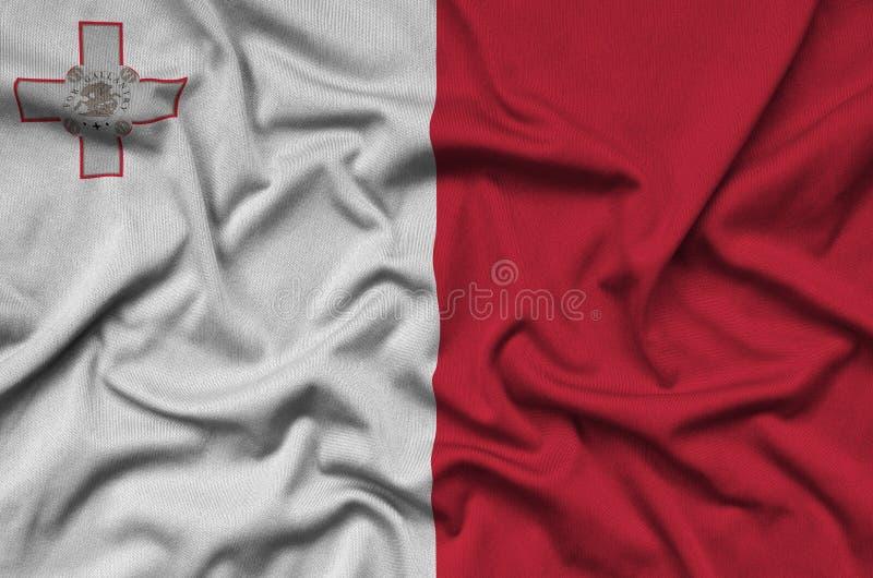 A bandeira de Malta é descrita em uma tela de pano dos esportes com muitas dobras Bandeira da equipe de esporte imagens de stock royalty free
