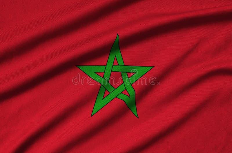 A bandeira de Marrocos é descrita em uma tela de pano dos esportes com muitas dobras Bandeira da equipe de esporte foto de stock