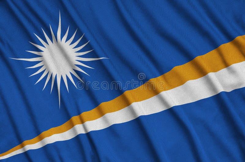 A bandeira de Marshall Islands é descrita em uma tela de pano dos esportes com muitas dobras Bandeira da equipe de esporte fotos de stock