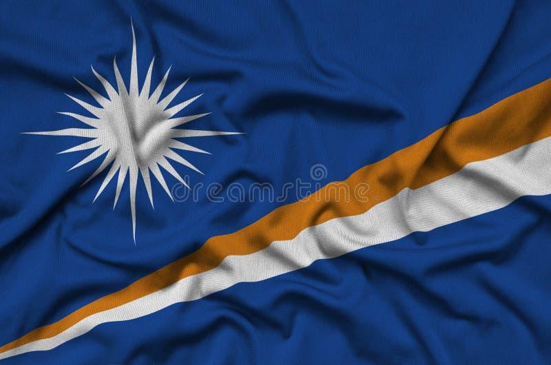 A bandeira de Marshall Islands é descrita em uma tela de pano dos esportes com muitas dobras Bandeira da equipe de esporte foto de stock royalty free