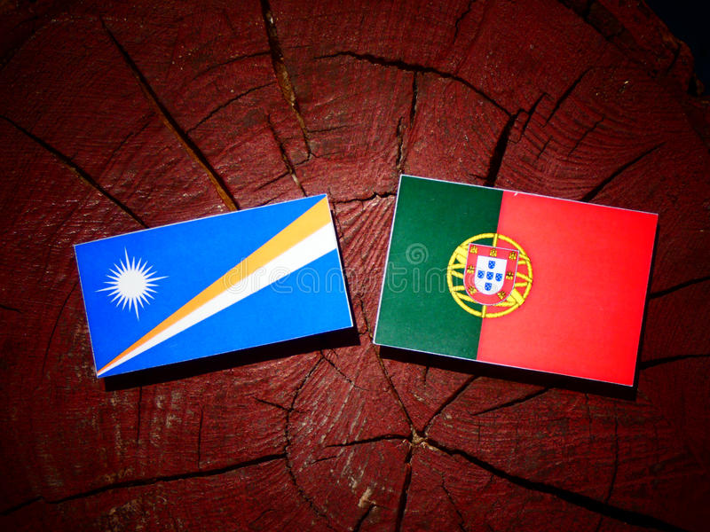 Bandeira de Marshall Islands com bandeira portuguesa em um isola do coto de árvore fotos de stock