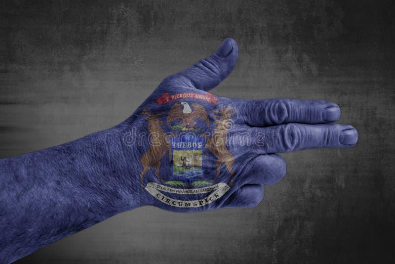 A bandeira de Michigan do estado de E.U. pintou na mão masculina como uma arma ilustração do vetor