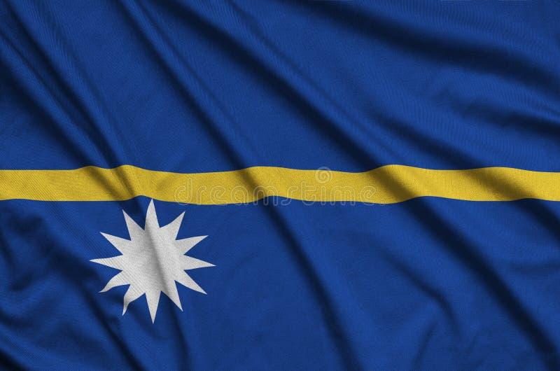 A bandeira de Nauru é descrita em uma tela de pano dos esportes com muitas dobras Bandeira da equipe de esporte imagens de stock