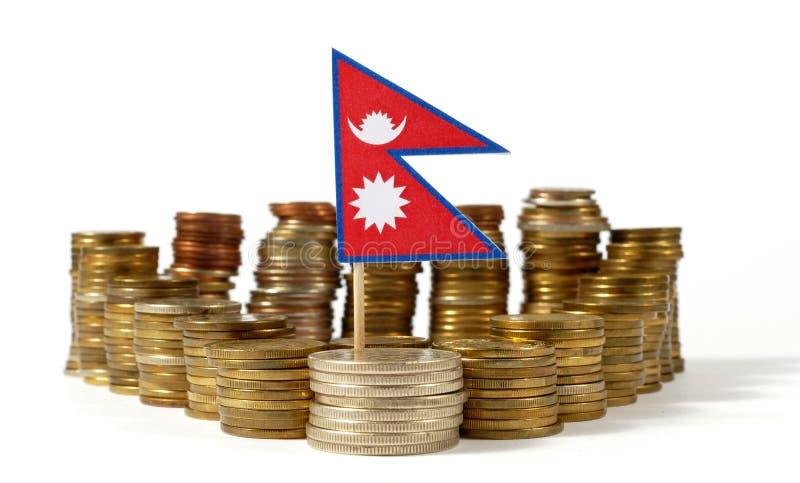 Bandeira de Nepal com a pilha de moedas do dinheiro imagem de stock royalty free