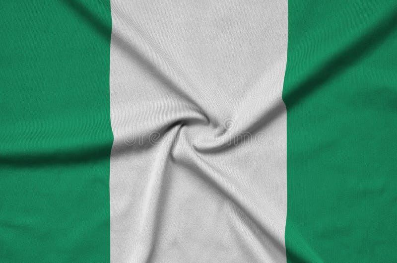 A bandeira de Nigéria é descrita em uma tela de pano dos esportes com muitas dobras Bandeira da equipe de esporte fotografia de stock royalty free