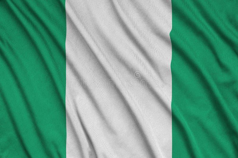 A bandeira de Nigéria é descrita em uma tela de pano dos esportes com muitas dobras Bandeira da equipe de esporte foto de stock royalty free