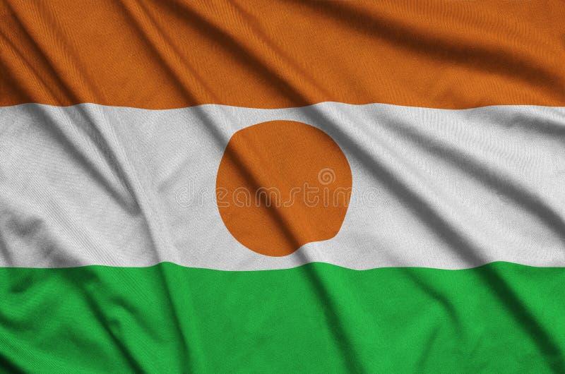 A bandeira de Niger é descrita em uma tela de pano dos esportes com muitas dobras Bandeira da equipe de esporte imagem de stock royalty free