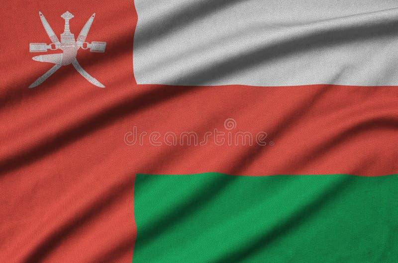 A bandeira de Omã é descrita em uma tela de pano dos esportes com muitas dobras Bandeira da equipe de esporte foto de stock royalty free