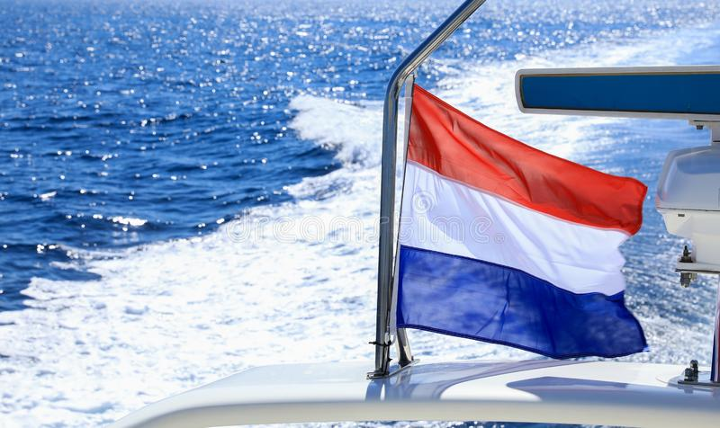 Bandeira de ondulação da Holanda na proa de um iate que viaja nas águas do Mar Egeu em Grécia fotografia de stock royalty free