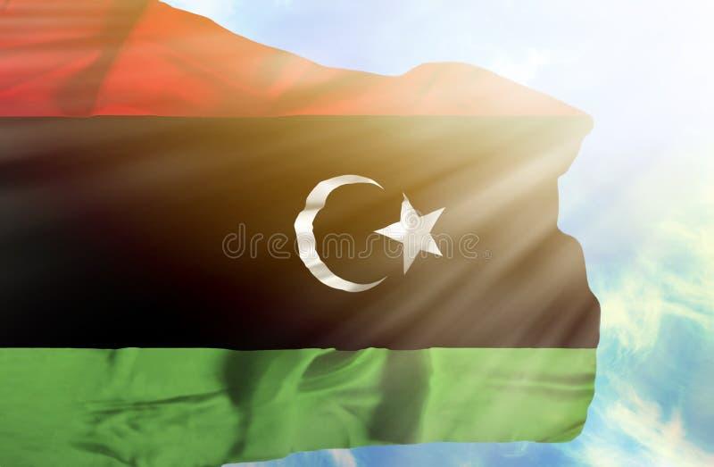 Bandeira de ondulação de Líbia contra o céu azul com raios de sol imagens de stock
