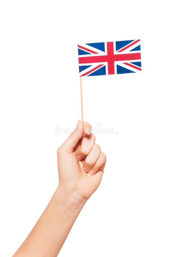 Bandeira de papel pequena de Grâ Bretanha na mão da mulher fotografia de stock