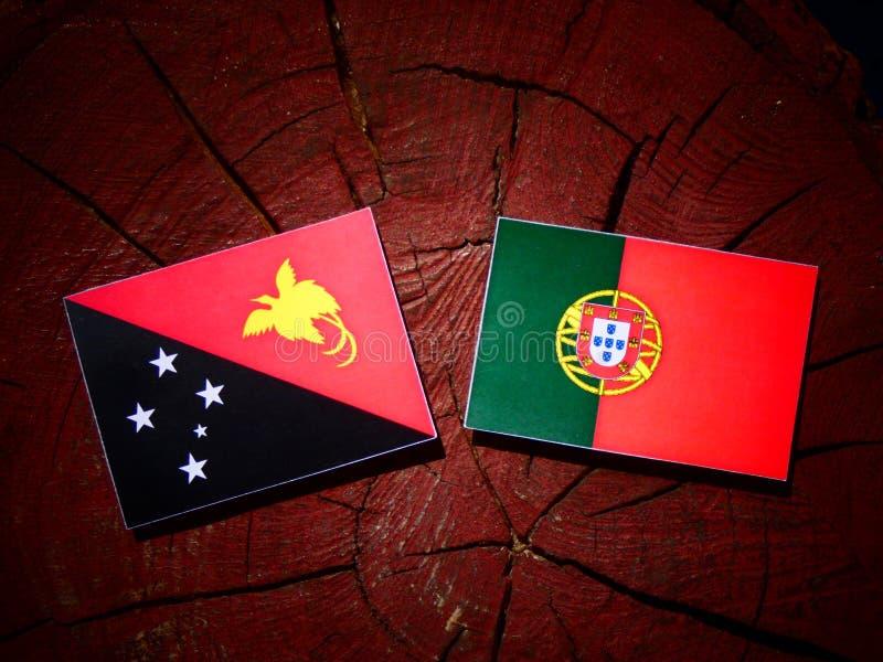 Bandeira de Papuásia-Nova Guiné com bandeira portuguesa em um isola do coto de árvore foto de stock royalty free