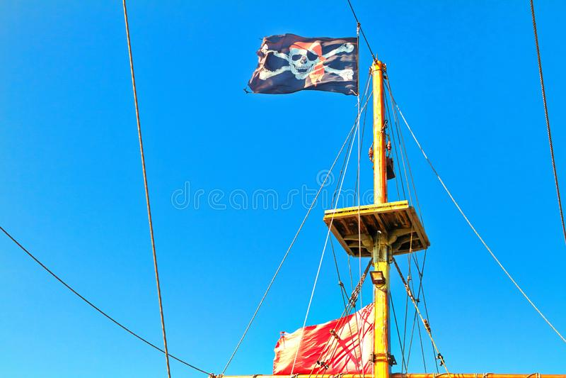 Bandeira de pirata içada contra o céu azul imagens de stock royalty free