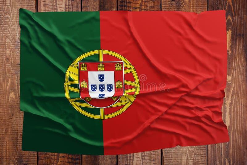 Bandeira de Portugal em um fundo de madeira da tabela Opini?o superior enrugada da bandeira portuguesa imagem de stock