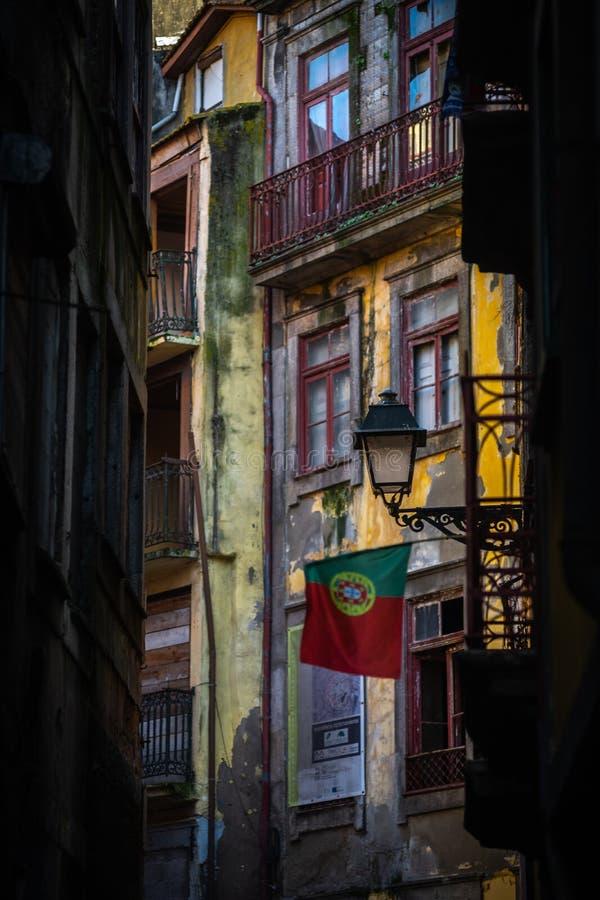 Bandeira de Portugal na rua de Porto com a casa do colorfull no fundo imagens de stock royalty free