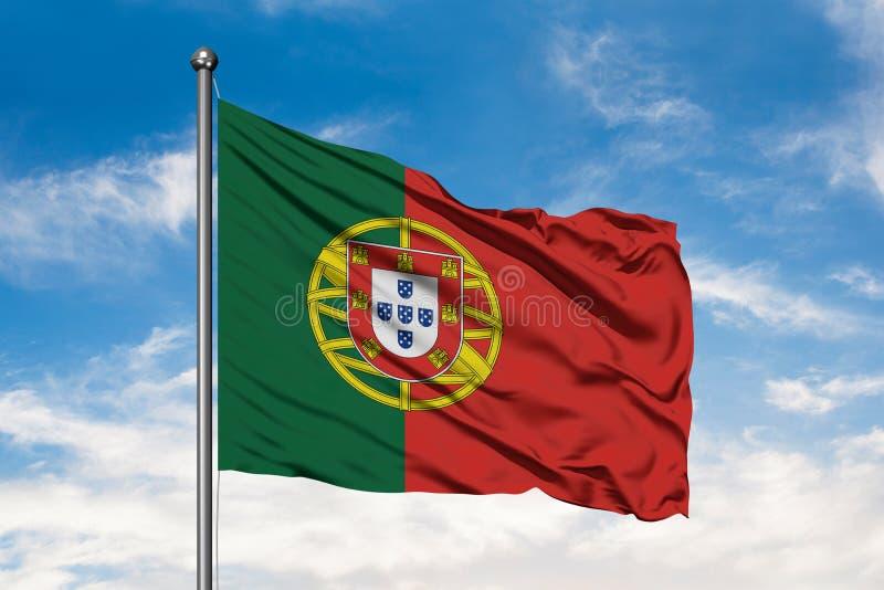 Bandeira de Portugal que acena no vento contra o céu azul nebuloso branco Bandeira portuguesa fotografia de stock royalty free