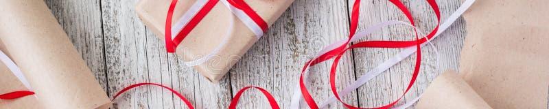 Bandeira de presentes de Natal de embalagem no papel de embalagem com as fitas vermelhas e brancas fotos de stock royalty free