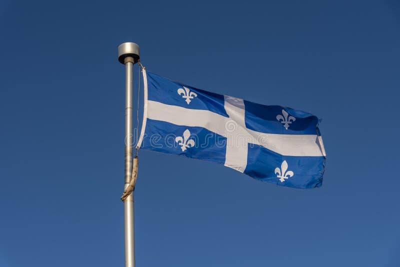 Bandeira de Quebeque contra o céu azul foto de stock royalty free
