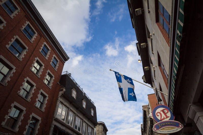 Bandeira de Quebeque na frente de um restaurante em Montreal velho, ou Vieux Montreal igualmente conhecido como Fleur de Lys, ou  fotos de stock
