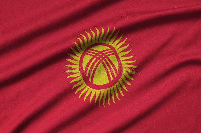 A bandeira de Quirguizistão é descrita em uma tela de pano dos esportes com muitas dobras Bandeira da equipe de esporte imagens de stock royalty free