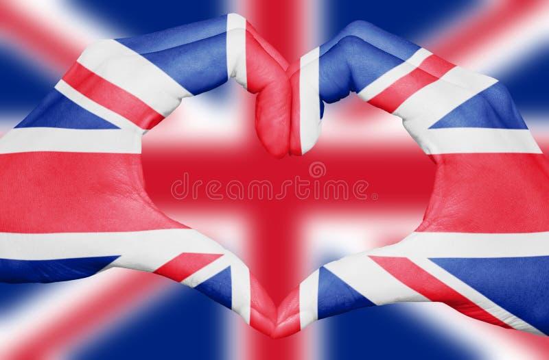 Bandeira de Reino Unido pintada nas mãos que formam um coração no fundo borrado de Union Jack, conceito BRITÂNICO do patriotismo imagens de stock
