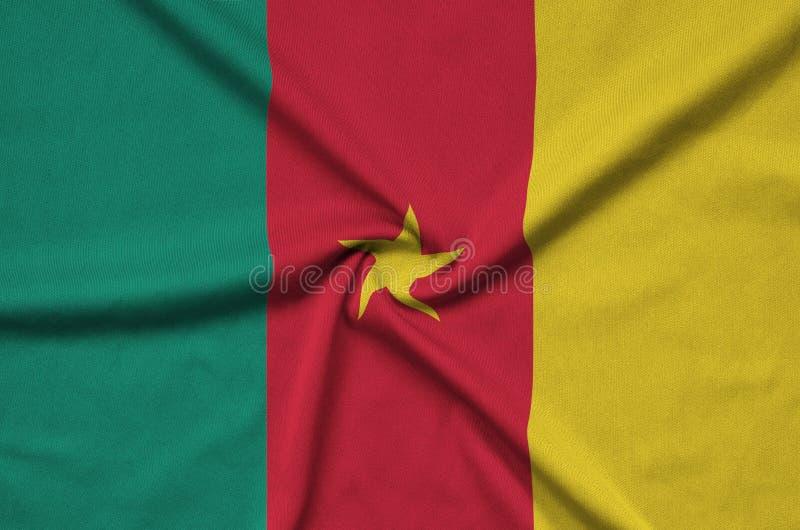 A bandeira de República dos Camarões é descrita em uma tela de pano dos esportes com muitas dobras Bandeira da equipe de esporte imagens de stock