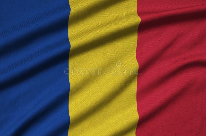 A bandeira de Romênia é descrita em uma tela de pano dos esportes com muitas dobras Bandeira da equipe de esporte imagem de stock royalty free