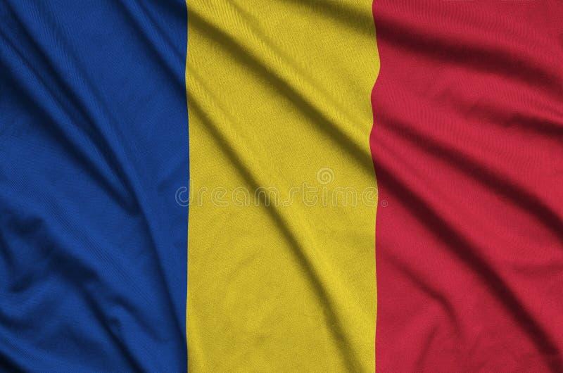 A bandeira de Romênia é descrita em uma tela de pano dos esportes com muitas dobras Bandeira da equipe de esporte imagens de stock royalty free