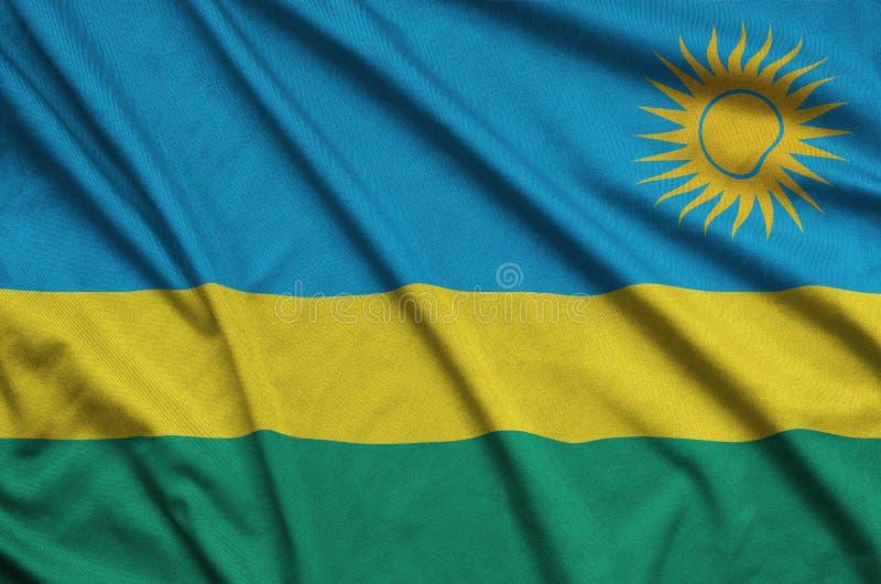 A bandeira de Ruanda é descrita em uma tela de pano dos esportes com muitas dobras Bandeira da equipe de esporte imagem de stock royalty free