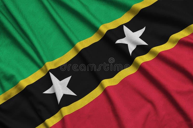 A bandeira de Saint Kitts e de Nevis é descrita em uma tela de pano dos esportes com muitas dobras Bandeira da equipe de esporte fotos de stock royalty free