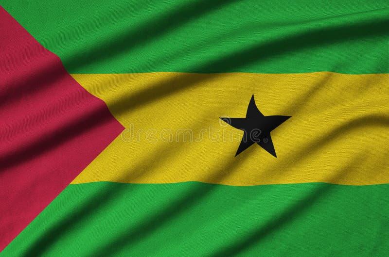 A bandeira de Sao Tome and Principe é descrita em uma tela de pano dos esportes com muitas dobras Bandeira da equipe de esporte fotografia de stock royalty free