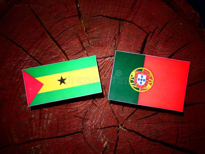 Bandeira de Sao Tome and Principe com bandeira portuguesa em um coto de árvore fotos de stock