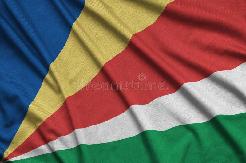 A bandeira de Seychelles é descrita em uma tela de pano dos esportes com muitas dobras Bandeira da equipe de esporte fotografia de stock royalty free