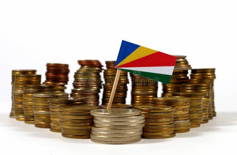 Bandeira de Seychelles com a pilha de moedas do dinheiro fotos de stock royalty free