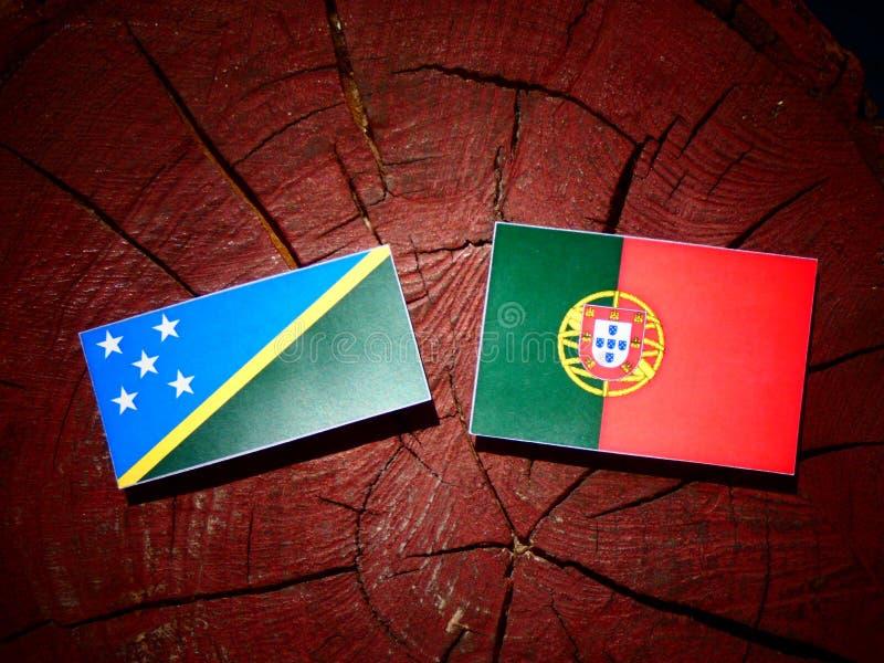 Bandeira de Solomon Islands com bandeira portuguesa em um isolat do coto de árvore foto de stock royalty free