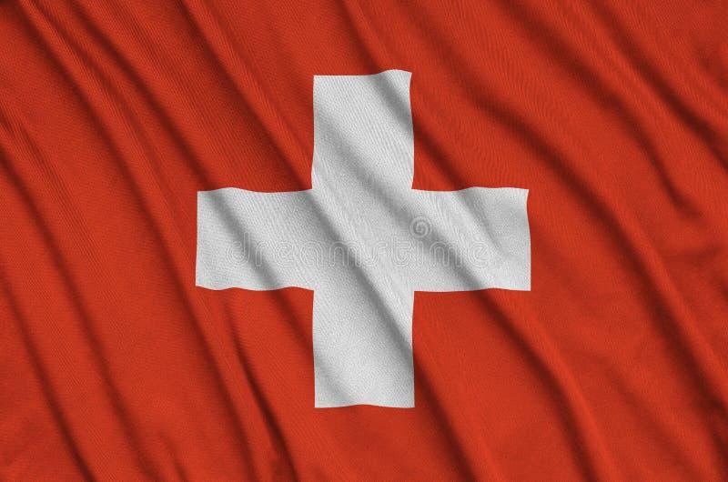 A bandeira de Suíça é descrita em uma tela de pano dos esportes com muitas dobras Bandeira da equipe de esporte imagens de stock royalty free