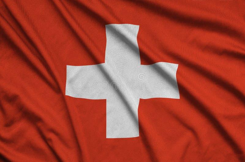 A bandeira de Suíça é descrita em uma tela de pano dos esportes com muitas dobras Bandeira da equipe de esporte imagem de stock royalty free