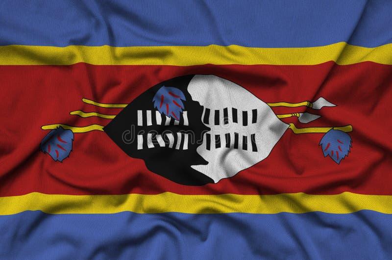 A bandeira de Suazilândia é descrita em uma tela de pano dos esportes com muitas dobras Bandeira da equipe de esporte fotografia de stock royalty free