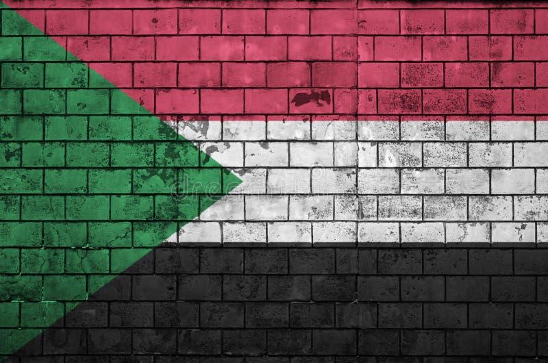 A bandeira de Sudão é pintada em uma parede de tijolo velha foto de stock