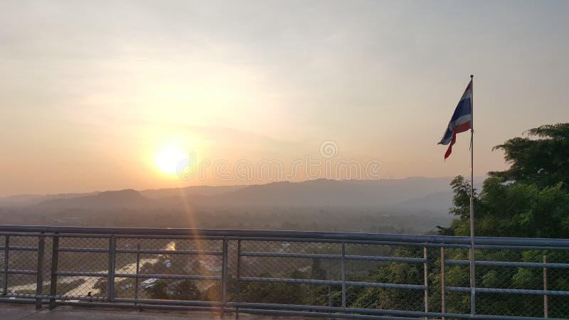 Bandeira de Tailândia acima da montanha e do por do sol no crepúsculo fotografia de stock royalty free
