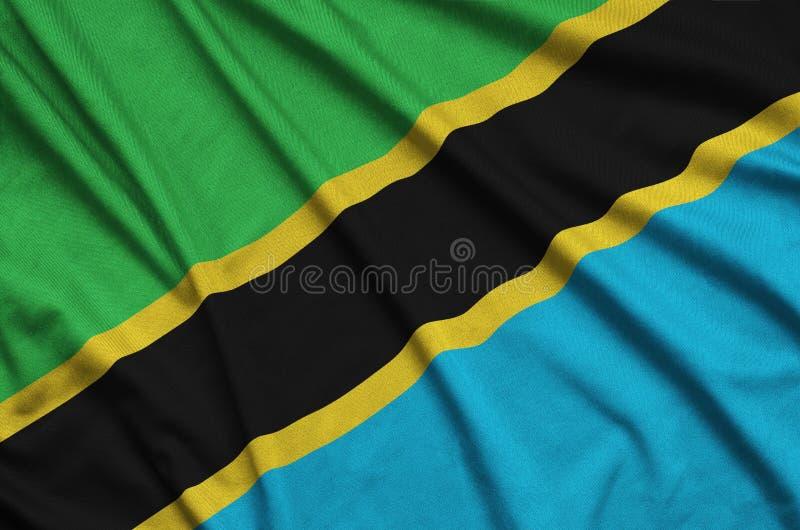 A bandeira de Tanzânia é descrita em uma tela de pano dos esportes com muitas dobras Bandeira da equipe de esporte imagem de stock royalty free