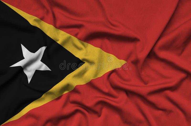 A bandeira de Timor-Leste é descrita em uma tela de pano dos esportes com muitas dobras Bandeira da equipe de esporte fotografia de stock