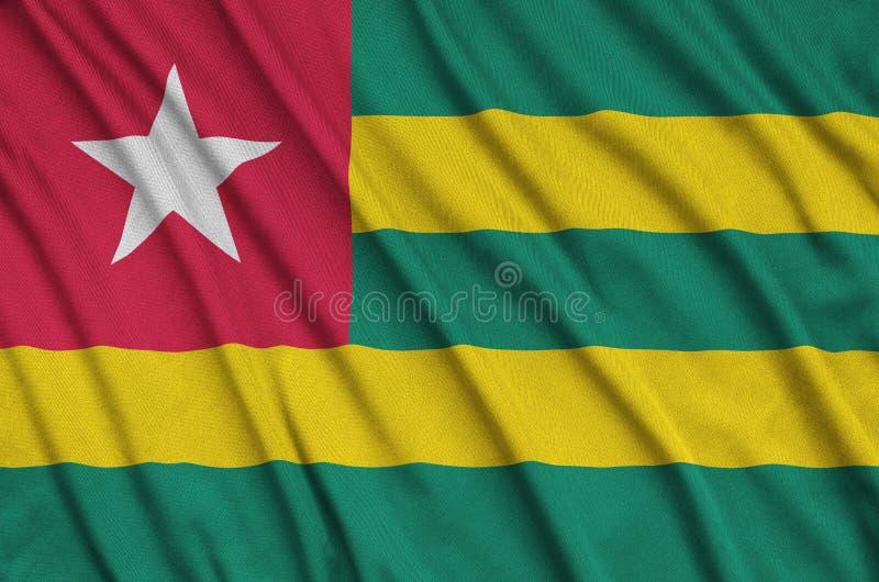 A bandeira de Togo é descrita em uma tela de pano dos esportes com muitas dobras Bandeira da equipe de esporte foto de stock royalty free