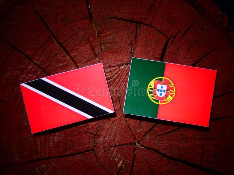 A bandeira de Trindade e Tobago com bandeira portuguesa em um coto de árvore é fotos de stock
