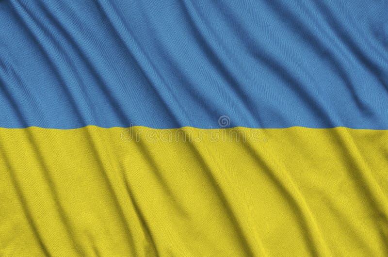 A bandeira de Ucrânia é descrita em uma tela de pano dos esportes com muitas dobras Bandeira da equipe de esporte imagem de stock royalty free