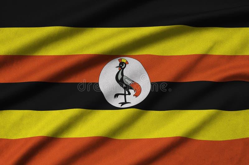 A bandeira de Uganda é descrita em uma tela de pano dos esportes com muitas dobras Bandeira da equipe de esporte foto de stock royalty free
