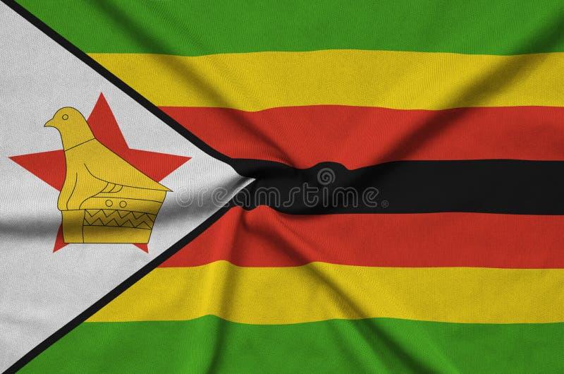 A bandeira de Zimbabwe é descrita em uma tela de pano dos esportes com muitas dobras Bandeira da equipe de esporte foto de stock