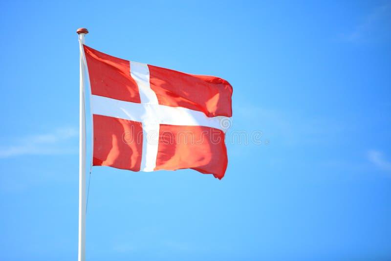 Bandeira dinamarquesa com o céu azul no fundo fotografia de stock