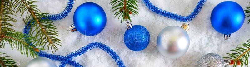 A bandeira do ano novo com as bolas azuis e de prata do Natal na neve, enfeita ramos verdes no fundo branco Decoração do Xmas foto de stock royalty free